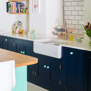 Large eclectic u-shaped kitchen/diner in Other with a belfast sink, shaker cabinets, blue cabinets, quartz worktops, white splashback, metro tiled splashback, painted wood flooring, an island, white floors and white appliances.