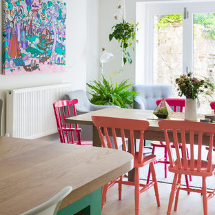 Photo of a large bohemian u-shaped kitchen/diner in Other with a belfast sink, shaker cabinets, blue cabinets, quartz worktops, white splashback, metro tiled splashback, an island, white appliances, painted wood flooring and white floors.
