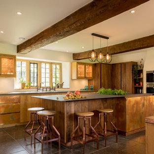 他の地域の広いカントリー風おしゃれなキッチン (ダブルシンク、フラットパネル扉のキャビネット、茶色いキャビネット、グレーの床) の写真