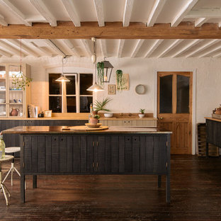 Photo of a country kitchen in Other with glass-front cabinets, beige cabinets, dark hardwood flooring and an island.