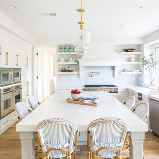 Coastal kitchen pictures - Inspiration for a coastal u-shaped medium tone wood floor and brown floor kitchen remodel in Los Angeles with a farmhouse sink, recessed-panel cabinets, white cabinets, stainless steel appliances and an island
