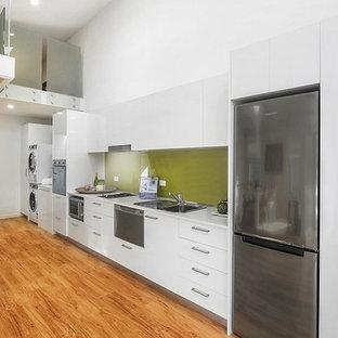 セントラルコーストの小さいトランジショナルスタイルのおしゃれなキッチン (ダブルシンク、フラットパネル扉のキャビネット、白いキャビネット、人工大理石カウンター、緑のキッチンパネル、ガラス板のキッチンパネル、シルバーの調理設備の、クッションフロア、アイランドなし) の写真