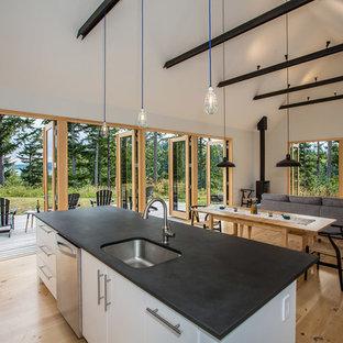 Foto de cocina rural, abierta, con fregadero bajoencimera, armarios con paneles lisos, puertas de armario blancas, encimera de acrílico, electrodomésticos de acero inoxidable, suelo de madera clara y una isla