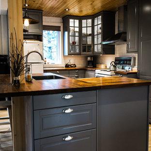 モントリオールの小さいラスティックスタイルのおしゃれなキッチン (シングルシンク、シェーカースタイル扉のキャビネット、グレーのキャビネット、木材カウンター、白いキッチンパネル、磁器タイルのキッチンパネル、白い調理設備、淡色無垢フローリング) の写真