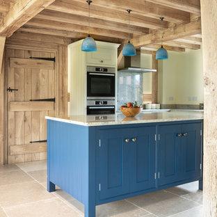 Farmhouse galley kitchen in West Midlands with shaker cabinets, blue cabinets, white splashback, stone slab splashback, stainless steel appliances, an island, beige floors and white worktops.