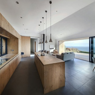 Design ideas for a modern galley open plan kitchen in Hampshire with a double-bowl sink, flat-panel cabinets, medium wood cabinets, wood worktops, glass sheet splashback, black appliances and an island.