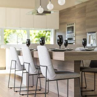 Geräumige Moderne Wohnküche in L-Form mit Unterbauwaschbecken, flächenbündigen Schrankfronten, grauen Schränken, Quarzit-Arbeitsplatte, Rückwand-Fenster, Küchengeräten aus Edelstahl, braunem Holzboden, zwei Kücheninseln und braunem Boden in Vancouver