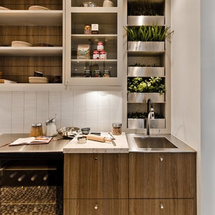 Example of a trendy kitchen design in Montreal with glass-front cabinets, matchstick tile backsplash, white backsplash, stainless steel countertops, an integrated sink and dark wood cabinets
