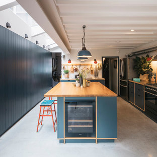 This is an example of a contemporary galley kitchen/diner in London with flat-panel cabinets, blue cabinets, wood worktops, beige splashback, porcelain splashback, concrete flooring, an island, grey floors and black appliances.