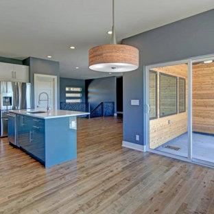 Idéer för ett mellanstort modernt vit kök, med en nedsänkt diskho, släta luckor, blå skåp, bänkskiva i onyx, vitt stänkskydd, stänkskydd i porslinskakel, rostfria vitvaror, laminatgolv, en köksö och brunt golv
