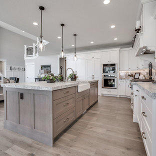 Mid-sized craftsman open concept kitchen ideas - Inspiration for a mid-sized craftsman l-shaped medium tone wood floor and brown floor open concept kitchen remodel in Salt Lake City with a farmhouse sink, shaker cabinets, white cabinets, marble countertops, white backsplash, subway tile backsplash, paneled appliances and an island