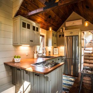 Rustikale Küche mit Landhausspüle, Schrankfronten im Shaker-Stil, grauen Schränken, Arbeitsplatte aus Holz, Küchengeräten aus Edelstahl, braunem Holzboden und Rückwand aus Holzdielen in Sonstige