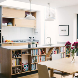 This is an example of a scandinavian kitchen/diner in Other with a submerged sink, flat-panel cabinets, black cabinets, black appliances, a breakfast bar, grey floors and grey worktops.