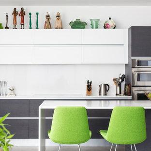 Cette image montre une grand cuisine minimaliste en L avec un évier 2 bacs, un placard à porte plane, un plan de travail en quartz modifié, une crédence blanche, un électroménager en acier inoxydable, un îlot central et des portes de placard blanches.