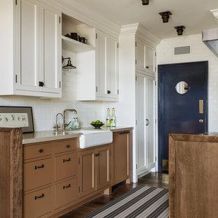 ロサンゼルスの小さいビーチスタイルのおしゃれなII型キッチン (エプロンフロントシンク、御影石カウンター、白いキッチンパネル、サブウェイタイルのキッチンパネル、茶色い床、落し込みパネル扉のキャビネット、茶色いキャビネット、パネルと同色の調理設備、濃色無垢フローリング、アイランドなし、ベージュのキッチンカウンター) の写真