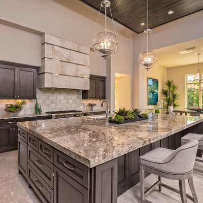 Open concept kitchen - large transitional marble floor and beige floor open concept kitchen idea in Austin with an undermount sink, dark wood cabinets, beige backsplash, stainless steel appliances, an island, granite countertops, subway tile backsplash and recessed-panel cabinets