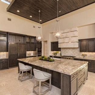 オースティンの巨大なラスティックスタイルのおしゃれなキッチン (アンダーカウンターシンク、シェーカースタイル扉のキャビネット、濃色木目調キャビネット、御影石カウンター、グレーのキッチンパネル、石タイルのキッチンパネル、パネルと同色の調理設備、磁器タイルの床、ベージュの床) の写真