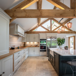 Design ideas for a country l-shaped kitchen in Other with a belfast sink, beaded cabinets, beige cabinets, wood worktops, multi-coloured splashback, stainless steel appliances, an island, beige floors, brown worktops and a vaulted ceiling.