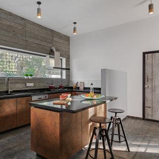 Cette image montre une cuisine design en U de taille moyenne avec un évier posé, un placard à porte plane, des portes de placard oranges, une crédence grise, une péninsule, un sol gris et un plan de travail noir.