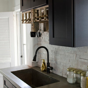 Photo of a mid-sized eclectic galley eat-in kitchen in Other with an integrated sink, shaker cabinets, black cabinets, concrete benchtops, white splashback, stone tile splashback, stainless steel appliances, laminate floors and a peninsula.