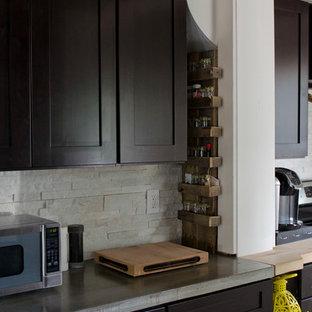 他の地域の中サイズのエクレクティックスタイルのおしゃれなキッチン (一体型シンク、シェーカースタイル扉のキャビネット、黒いキャビネット、コンクリートカウンター、白いキッチンパネル、石タイルのキッチンパネル、シルバーの調理設備の、ラミネートの床) の写真