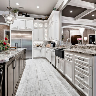 Inspiration for a large traditional u-shaped open plan kitchen in Other with a farmhouse sink, raised-panel cabinets, white cabinets, granite benchtops, brown splashback, glass tile splashback, white appliances, porcelain floors, with island, beige floor and brown benchtop.