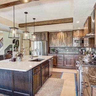 他の地域の大きいラスティックスタイルのおしゃれなキッチン (シングルシンク、シェーカースタイル扉のキャビネット、ヴィンテージ仕上げキャビネット、珪岩カウンター、マルチカラーのキッチンパネル、レンガのキッチンパネル、シルバーの調理設備の、濃色無垢フローリング、茶色い床、白いキッチンカウンター) の写真