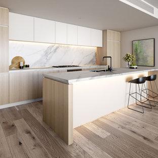 メルボルンの広いコンテンポラリースタイルのおしゃれなキッチン (ダブルシンク、淡色木目調キャビネット、タイルカウンター、磁器タイルのキッチンパネル、シルバーの調理設備、淡色無垢フローリング) の写真