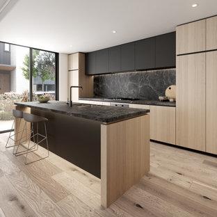 メルボルンの広いコンテンポラリースタイルのおしゃれなキッチン (タイルカウンター、ダブルシンク、落し込みパネル扉のキャビネット、黒いキッチンパネル、磁器タイルのキッチンパネル、黒い調理設備、淡色無垢フローリング、黒いキッチンカウンター) の写真