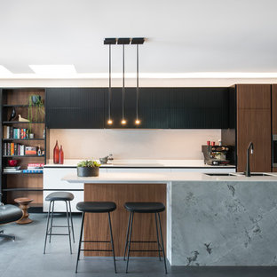 This is an example of a large contemporary l-shaped open plan kitchen in Sydney with a double-bowl sink, flat-panel cabinets, solid surface benchtops, grey splashback, stainless steel appliances, porcelain floors, with island, black floor, white benchtop and dark wood cabinets.