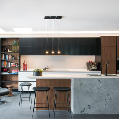 Example of a large trendy l-shaped porcelain tile and black floor open concept kitchen design in Sydney with a double-bowl sink, flat-panel cabinets, solid surface countertops, gray backsplash, stainless steel appliances, an island, white countertops and dark wood cabinets