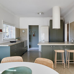 Contemporary u-shaped kitchen in Melbourne with flat-panel cabinets, green cabinets, white appliances, a peninsula, brown floor and beige benchtop.
