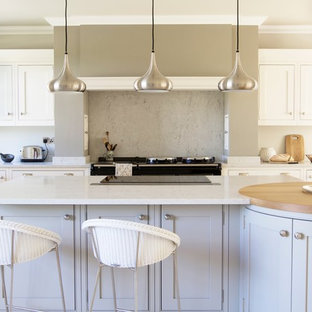Country l-shaped kitchen in West Midlands with shaker cabinets, white cabinets, grey splashback, marble splashback, an island, beige floors and grey worktops.