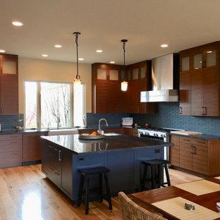 Idéer för att renovera ett stort orientaliskt grå grått kök, med en rustik diskho, släta luckor, skåp i mellenmörkt trä, bänkskiva i kvartsit, blått stänkskydd, stänkskydd i glaskakel, rostfria vitvaror, bambugolv, en köksö och brunt golv
