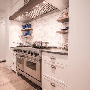 タンパの中サイズのエクレクティックスタイルのおしゃれなキッチン (アンダーカウンターシンク、シェーカースタイル扉のキャビネット、白いキャビネット、ライムストーンカウンター、白いキッチンパネル、サブウェイタイルのキッチンパネル、パネルと同色の調理設備、淡色無垢フローリング、ベージュの床、グレーのキッチンカウンター) の写真