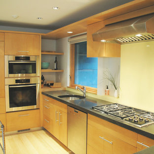 Photo of a mid-sized midcentury u-shaped open plan kitchen in Other with an undermount sink, flat-panel cabinets, medium wood cabinets, concrete benchtops, yellow splashback, glass sheet splashback, stainless steel appliances and light hardwood floors.