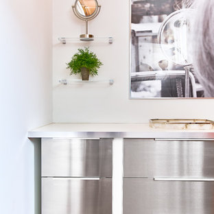 This is an example of a small scandinavian single-wall kitchen pantry in Providence with an integrated sink, flat-panel cabinets, stainless steel cabinets, quartz worktops, white splashback, stainless steel appliances, medium hardwood flooring, brown floors and white worktops.