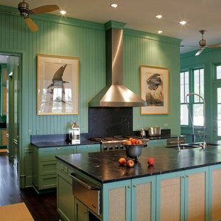 Example of a farmhouse kitchen design in Atlanta with an undermount sink, recessed-panel cabinets, green cabinets, soapstone countertops, black backsplash, stone slab backsplash and stainless steel appliances