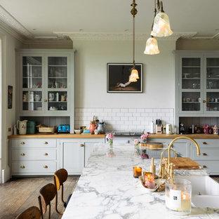 他の地域の大きいエクレクティックスタイルのおしゃれなペニンシュラキッチン (シェーカースタイル扉のキャビネット、グレーのキャビネット) の写真