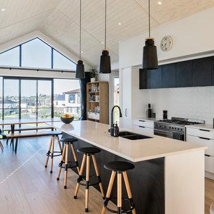オークランドのモダンスタイルのおしゃれなキッチン (ダブルシンク、フラットパネル扉のキャビネット、黒いキャビネット、白いキッチンパネル、黒い調理設備、淡色無垢フローリング、ベージュの床、白いキッチンカウンター) の写真