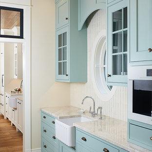 Zweizeilige, Mittelgroße Klassische Küche mit Vorratsschrank, Landhausspüle, Schrankfronten im Shaker-Stil, blauen Schränken, Kalkstein-Arbeitsplatte, Küchenrückwand in Weiß, Rückwand aus Keramikfliesen, Keramikboden, buntem Boden und beiger Arbeitsplatte in Grand Rapids