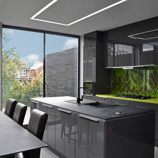 Photo of a contemporary galley kitchen/diner in London with a built-in sink, flat-panel cabinets, black cabinets, green splashback and black appliances.