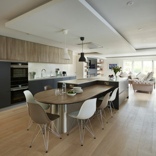 Contemporary single-wall open plan kitchen in Berkshire with flat-panel cabinets, light wood cabinets, black appliances, light hardwood floors, with island and beige floor.