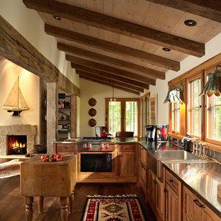 Diseño de cocina rústica, abierta, con fregadero integrado, encimera de acero inoxidable, armarios estilo shaker y electrodomésticos de acero inoxidable