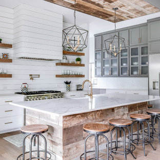 Farmhouse kitchen ideas - Example of a farmhouse light wood floor and gray floor kitchen design in Dallas with a farmhouse sink, shaker cabinets, gray cabinets, quartz countertops, white backsplash, wood backsplash, stainless steel appliances, an island and white countertops