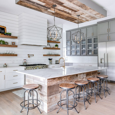 Example of a country l-shaped light wood floor and beige floor kitchen design in Dallas with a farmhouse sink, shaker cabinets, quartz countertops, white backsplash, wood backsplash, stainless steel appliances, an island, white countertops and white cabinets
