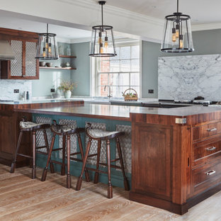 Large traditional u-shaped kitchen/diner in Other with a belfast sink, marble worktops, marble splashback, stainless steel appliances, an island, white worktops, recessed-panel cabinets, green cabinets, white splashback, medium hardwood flooring and brown floors.