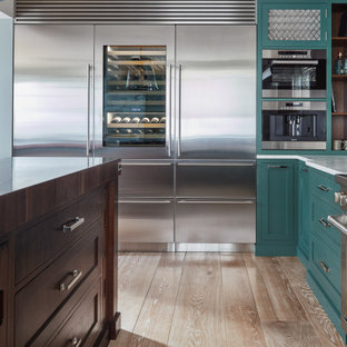 Design ideas for a large eclectic u-shaped eat-in kitchen in Other with a farmhouse sink, shaker cabinets, turquoise cabinets, marble benchtops, yellow splashback, marble splashback, stainless steel appliances, light hardwood floors, with island, multi-coloured floor and white benchtop.