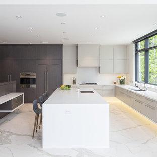 Foto på ett funkis kök, med en undermonterad diskho, släta luckor, grå skåp, vitt stänkskydd, integrerade vitvaror, marmorgolv, en köksö och vitt golv