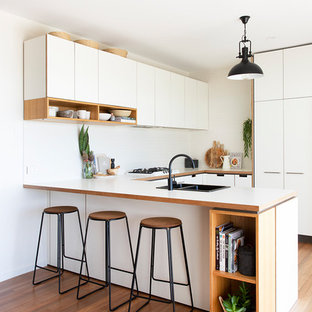 Photo of a beach style u-shaped kitchen in Gold Coast - Tweed with a double-bowl sink, flat-panel cabinets, white cabinets, white splashback, light hardwood floors, a peninsula, beige floor and white benchtop.